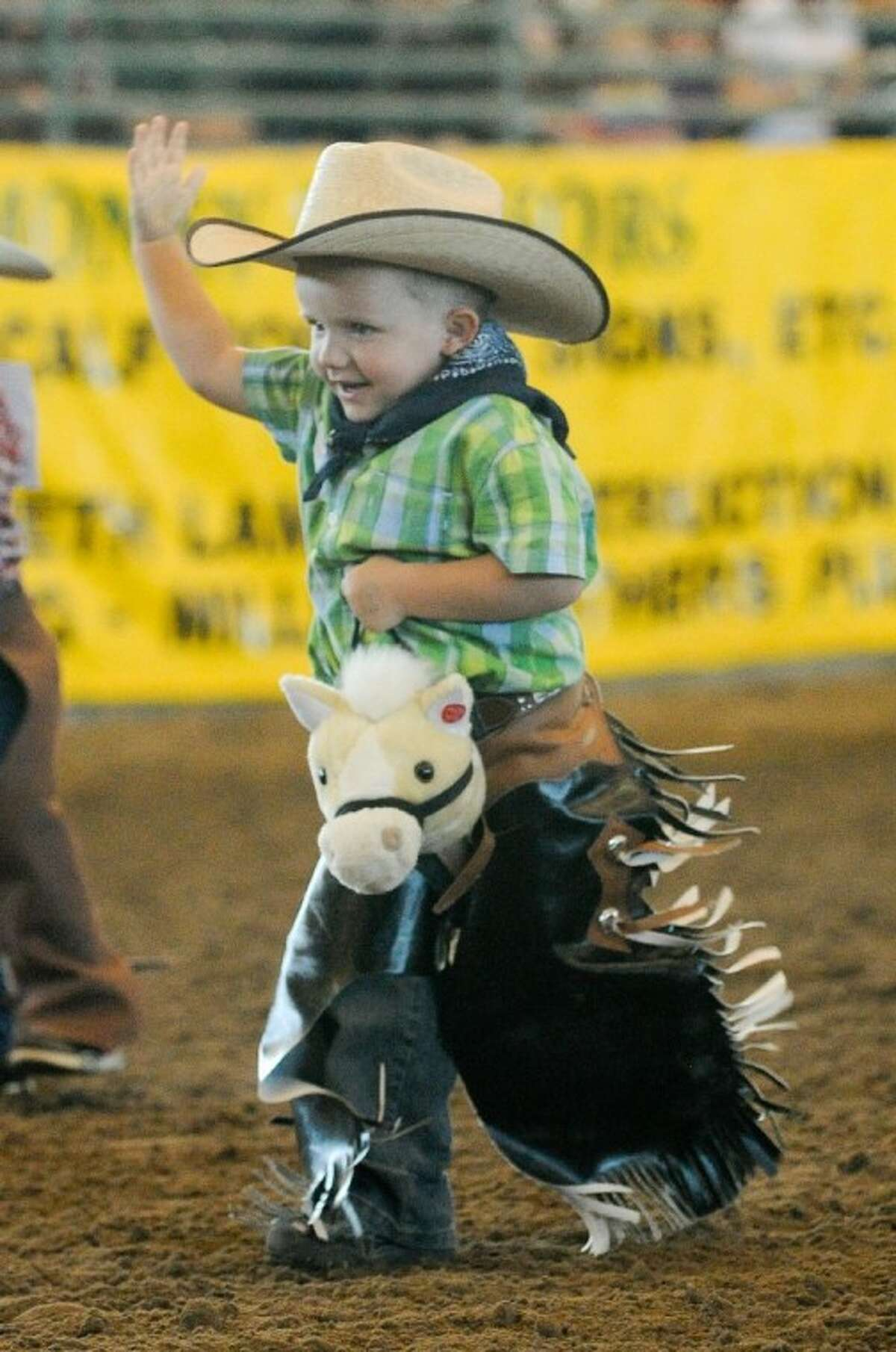 A youngster enjoys the stick horse race at the rodeo.