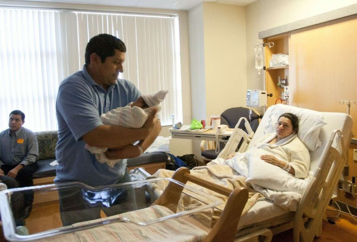Newborn Thiago Jace Marquez is picked up by father Pedro as mother Maria looks on Saturday at St. Luke's Hospital in The Woodlands.