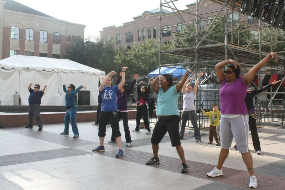 A group of women exercise and do dance moves at the Fitness in the Plaza Zumba classes at Town Square on Monday. The free classes are offered every Friday at 10 a.m.