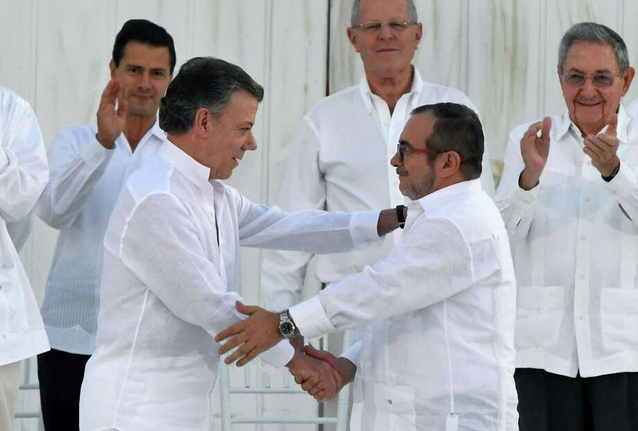 "Colombian President Juan Manuel Santos (2-L) and the head of the FARC guerrilla Timoleon Jimenez, aka Timochenko, shake hands during the signing of the historic peace agreement between the Colombian government and the Revolutionary Armed Forces of Colombia (FARC), in Cartagena, Colombia, on September 26, 2016  Colombia will turn the page on a half-century conflict that has stained its modern history with blood when the FARC rebels and the government sign a peace deal on Monday. President Juan Manuel Santos and the leader of the FARC, Rodrigo Londono -- better known by his nom de guerre, Timoleon ""Timochenko"" Jimenez -- are set to sign the accord at 2200 GMT in a ceremony in the colorful colonial city of Cartagena on the Caribbean coast. Photo: LUIS ACOSTA, AFP/Getty Images / AFP or licensors"