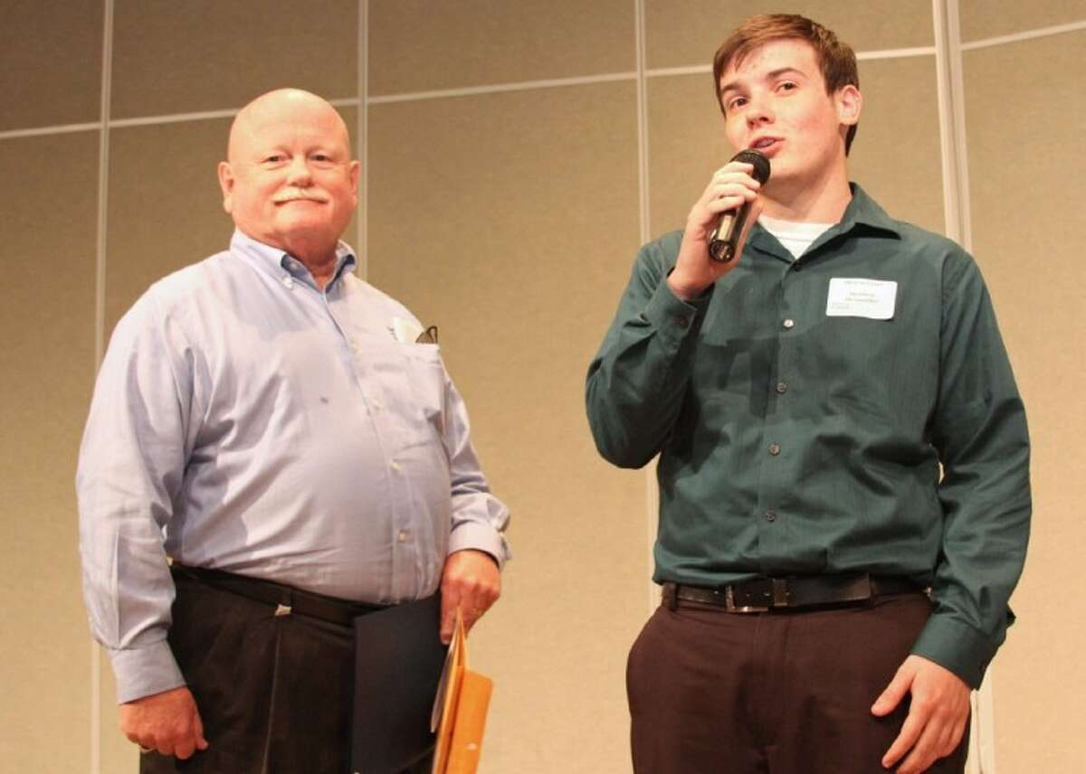 Current Pearland ISD board president Virgil Gant (left) presents a scholarship to a Pearland High School student during the 2011 Dare to Excel luncheon.