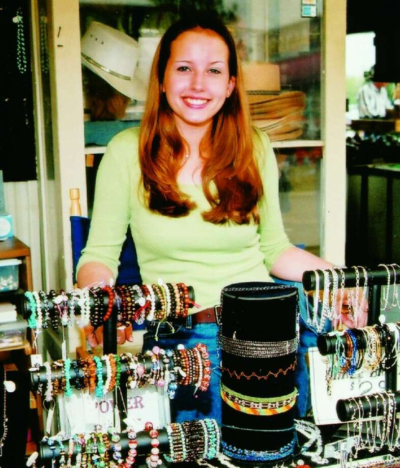 A jewelry vendor shows off some of her wares that are sold at Traders Village in Houston.