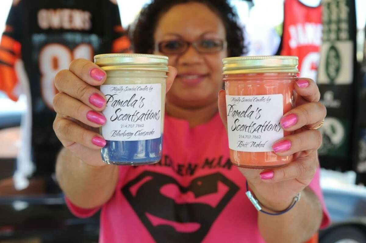 A candle vendor shows off some the candles she sells at Traders Village in Houston.
