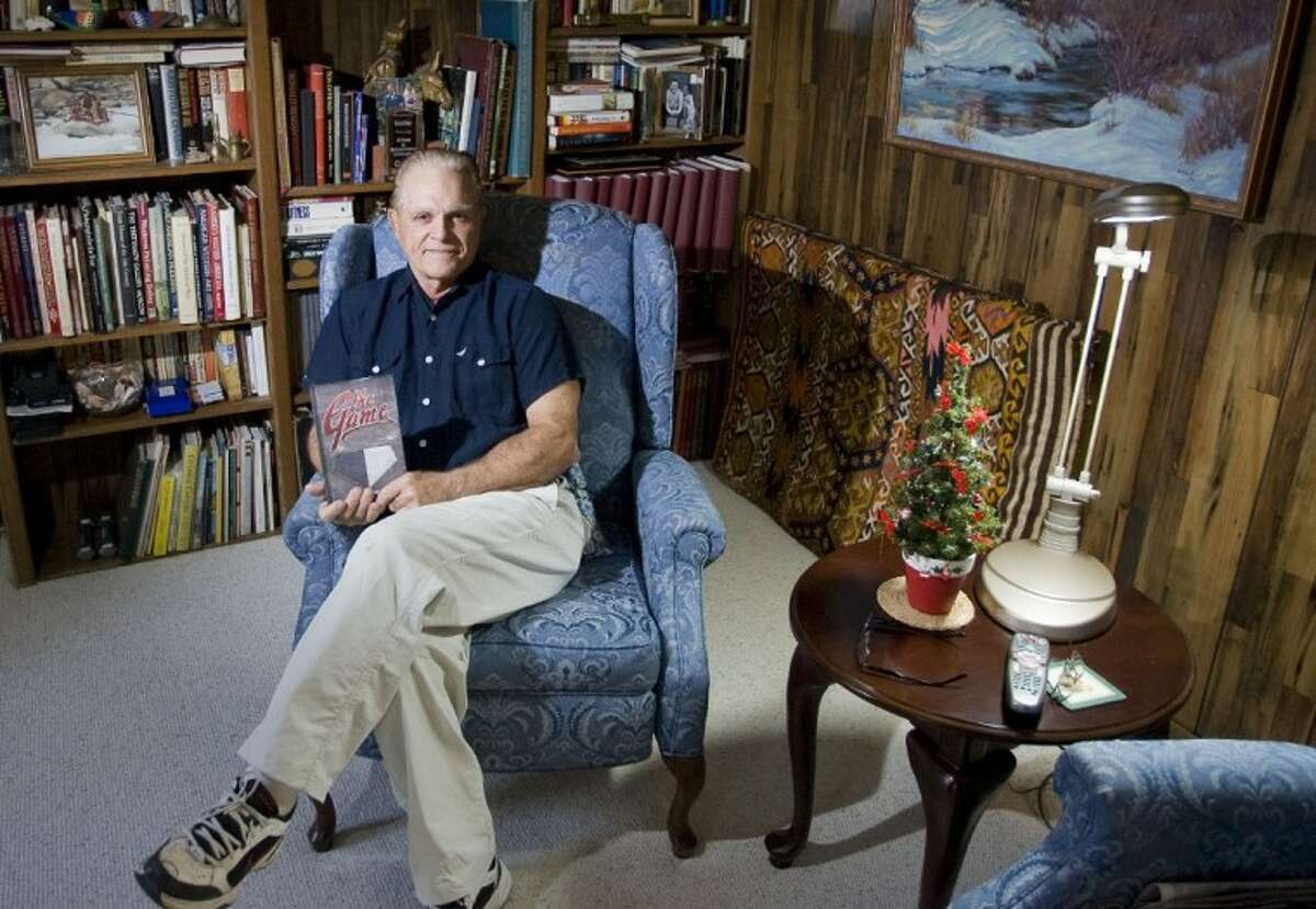 Author Franklin Kless is photographed at his home in The Woodlands with his book,
