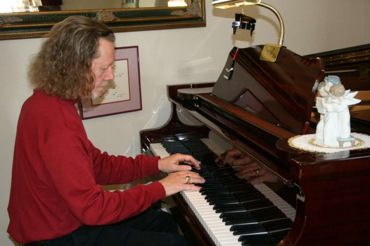 Local pianist Ed White practices on his baby grand piano at home. He purchased the piano a year after he began playing the keyboard at 53 years old, with no musical background.