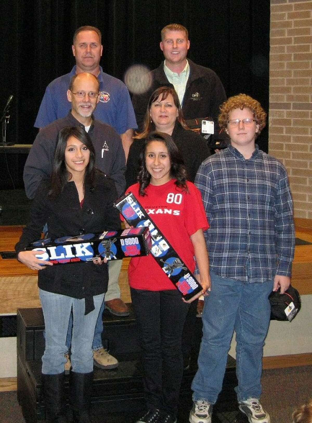 Pictured front row left to right, Perla Agular, Melissa Espita and Cameron Gaylord hold tripods and cases donated by Yokom Properties. Middle row Vince and Robin Yokom. Back row, Gerald Powell, WCFA president and Royal High School video instructor Chase Jacobs.