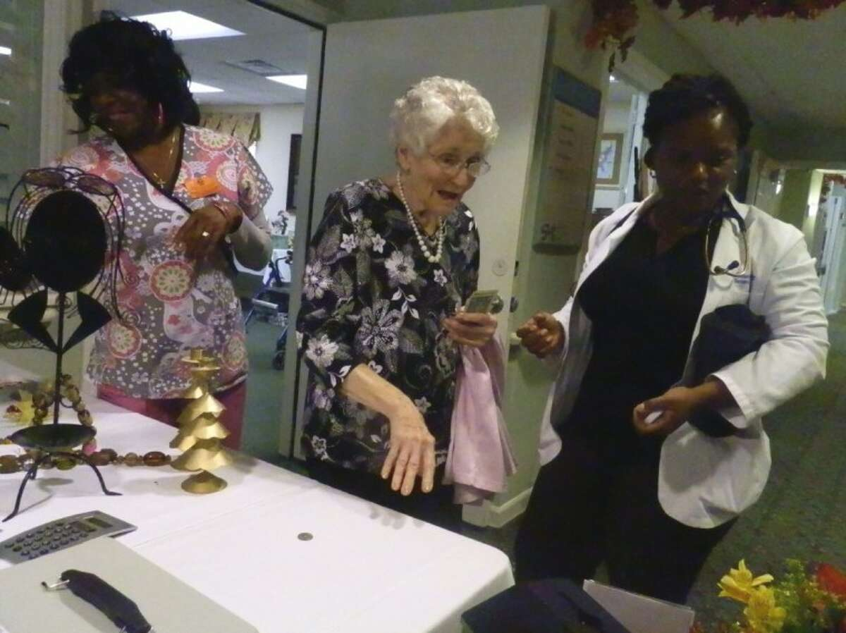 Regina Wells, Eunice Alleman and Abby Williams take a look around at the gently used sale held by Parkway Place residents to raise money for a family in need.
