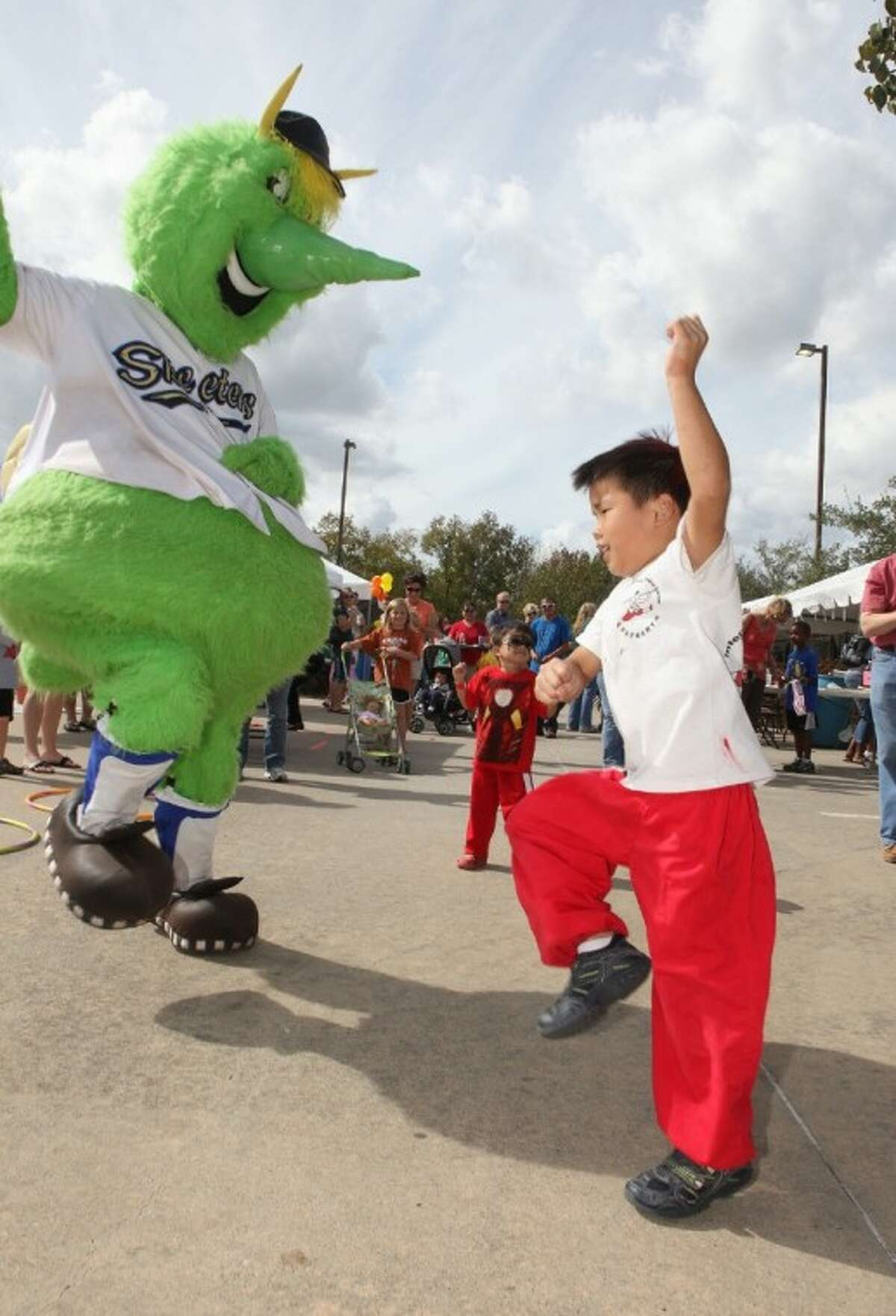 Kyle Lew, 6, of Missouri City dances Gangnam Style with Sugar Land Skeeters mascot Swatson at the First United Methodist Church Missouri City Fall Festival on Nov. 10.