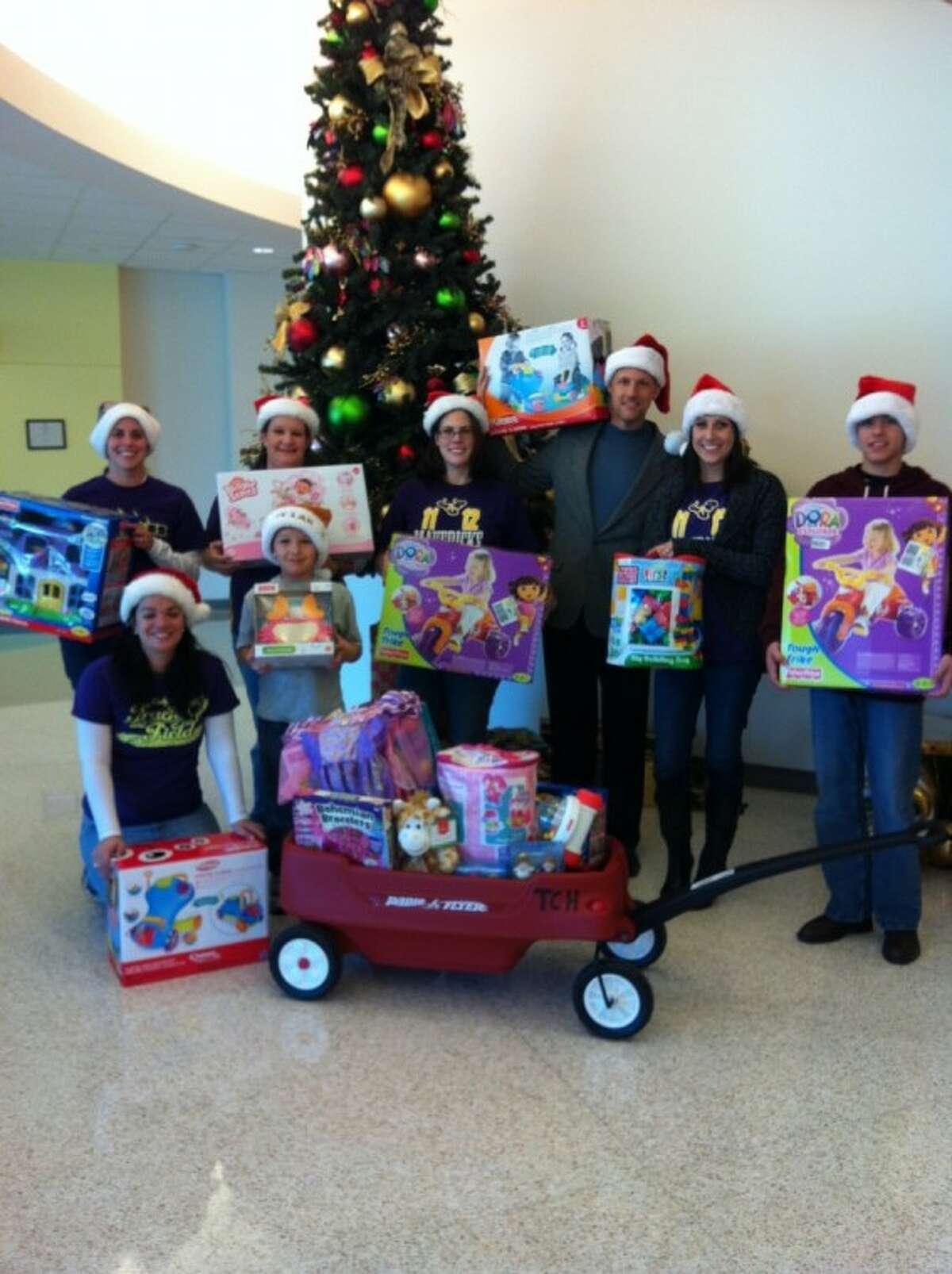 Morton Ranch Junior High language arts teachers Sara Brownlee (kneeling on floor), Kristin Bell, Kim Klingbeil, Piper Taylor, Mark McCord (school principal) and Rachel Tate, along with two students, delivered 416 toys donated by students for children fighting illnesses at Texas Children's Hospital West Campus.