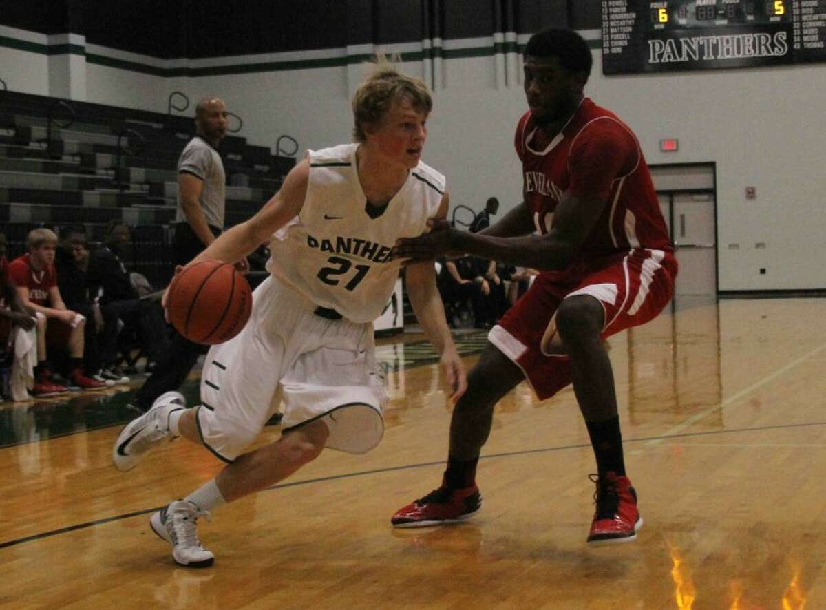 Kingwood Park's Caleb Mattson (21) drives past Cleveland post Cedric Gambrell (40) during a high school boys basketball game at Kingwood Park High School on Jan. 4, 2013. Cleveland defeated Kingwood Park 58-54. Go to HCNpics.com to see more photos from the game.