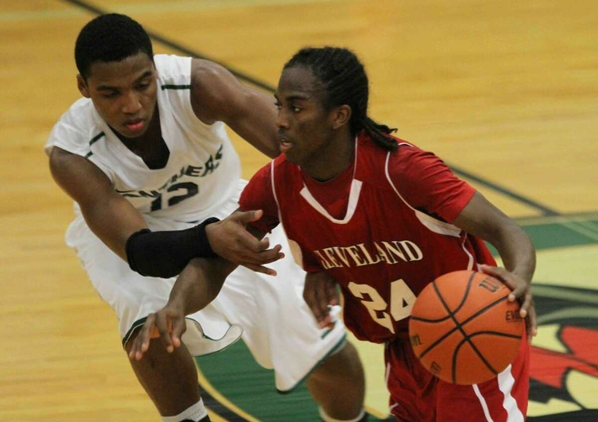 Cleveland guard Deon Baldwin (24) drives past Kingwood Park's Jaylen Henderson (15) during a high school boys basketball game at Kingwood Park High School on Jan. 4, 2013. Cleveland defeated Kingwood Park 58-54. Go to HCNpics.com to see more photos from the game.