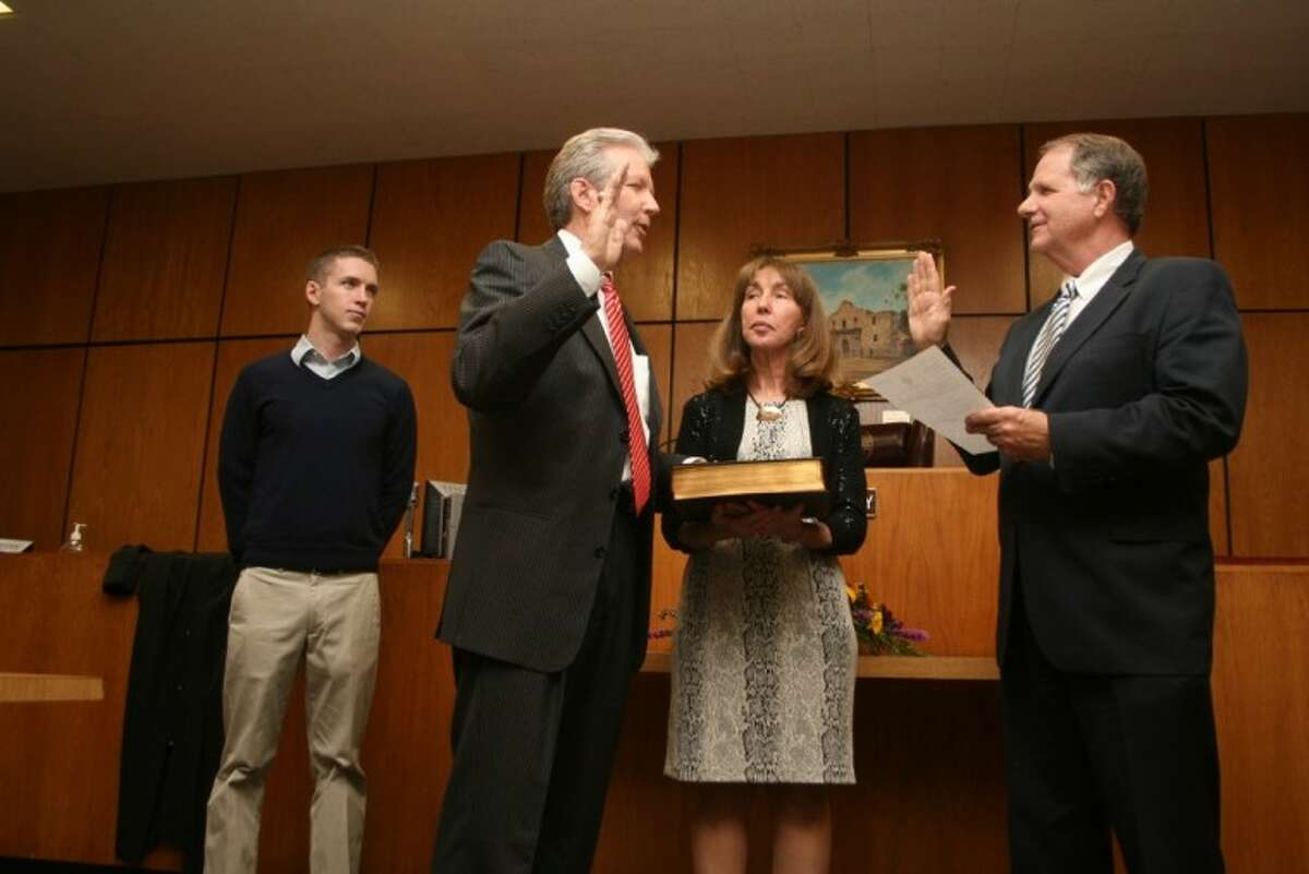 Baytown attorney Don Coffey is sworn in as the new Harris County Justice of the Peace, Pct. 3, Place 2, replacing the retiring Judge Tony Polumbo. The Democrat invited his Republican congressman U. S. Rep. Ted Poe to swear him in. His wife Jenice holds the Bible while his son Stephen looks on.