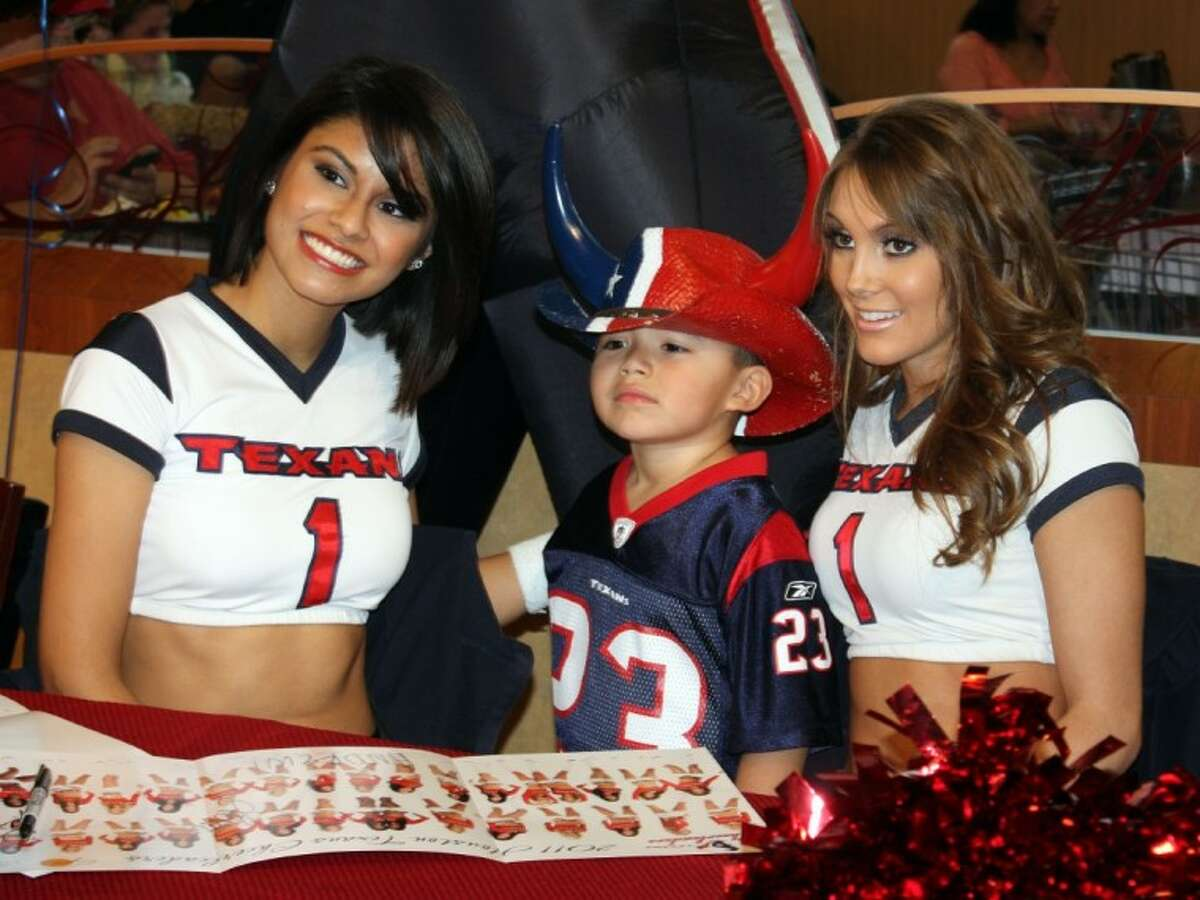 Four-year-old Andres Castillo, the son of Jessica Castillo, has his picture taken Thursday afternoon with Houston Texans cheerleaders Liliana and Lexa at the Kroger store on the Grand Parkway.
