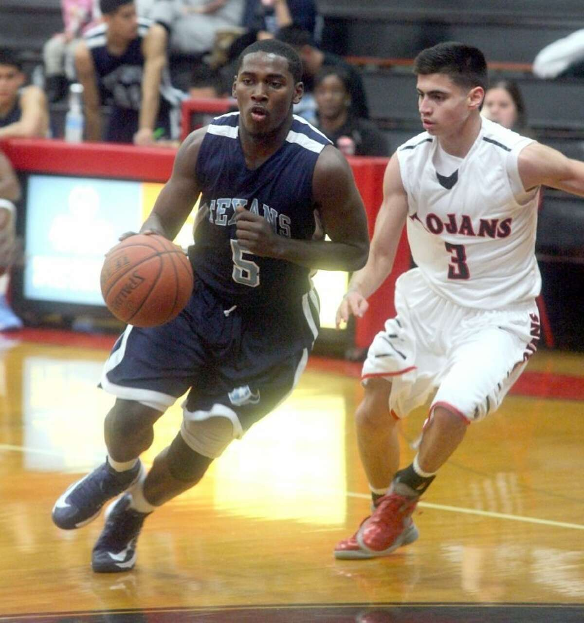 Rayburn's LaTrone Williams attempts to dribble past the defense of Felipe Salinas during Friday night's game in the Trojan Gym. Williams and Co. gave the hosts a mini scare but the Trojans hung on for an eight-point win.