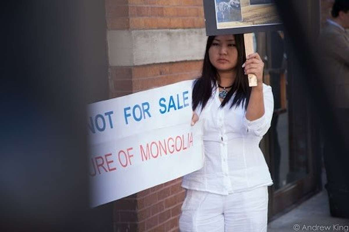 A woman protests the sale of Tyrannosaurus bones found buried in Mongolia.