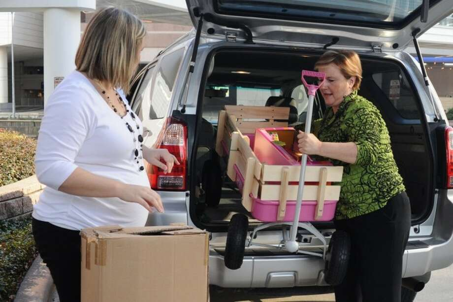 The Rose staff members Michelle Hanson and Karen Campbell unload toys purchased during The Rose Annual Shrimp Boil Live Auction and then donated back to Texas Children's Hospital Thursday, Dec. 5.