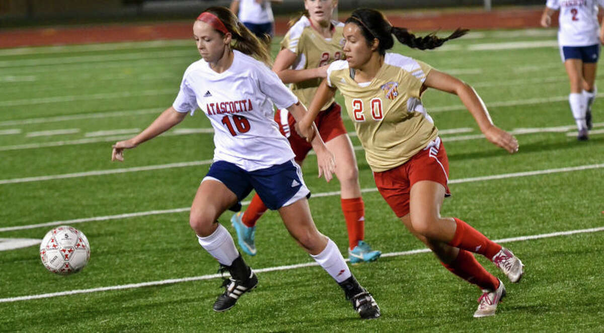Emily Richardson (16) and Ashley Ayala (20) chase after a loose ball during a high school soccer match between Atascocita and Cy Woods in the opening round of the Humble ISD Women's Soccer Invitational on Jan. 10 at Turner Stadium in Humble.