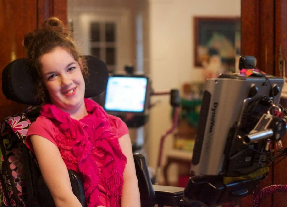 Megan Fry, who suffers from cerebral palsy, smiles as she sits with her custom computer, which she controls via movements from her eyes, and allows her to speak.