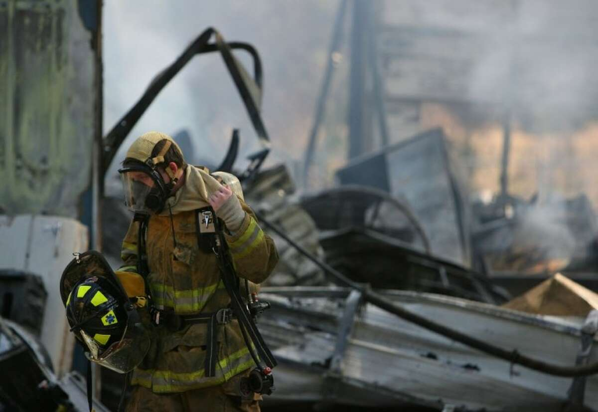 A firefighter exits the scene of a commercial fire Jan. 5 at Prestige Automotive Restoration on Sawdust Road in The Woodlands