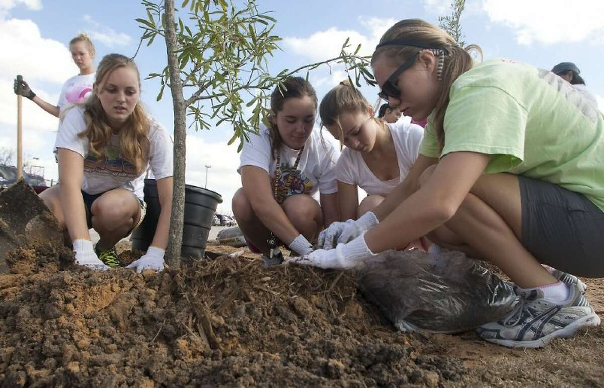 St. Agnes Academy students Angela Ott, Caroline Matlock, Hannah Kendall, and Hannah McAughan volunteer to plant trees around the athletic field complex.