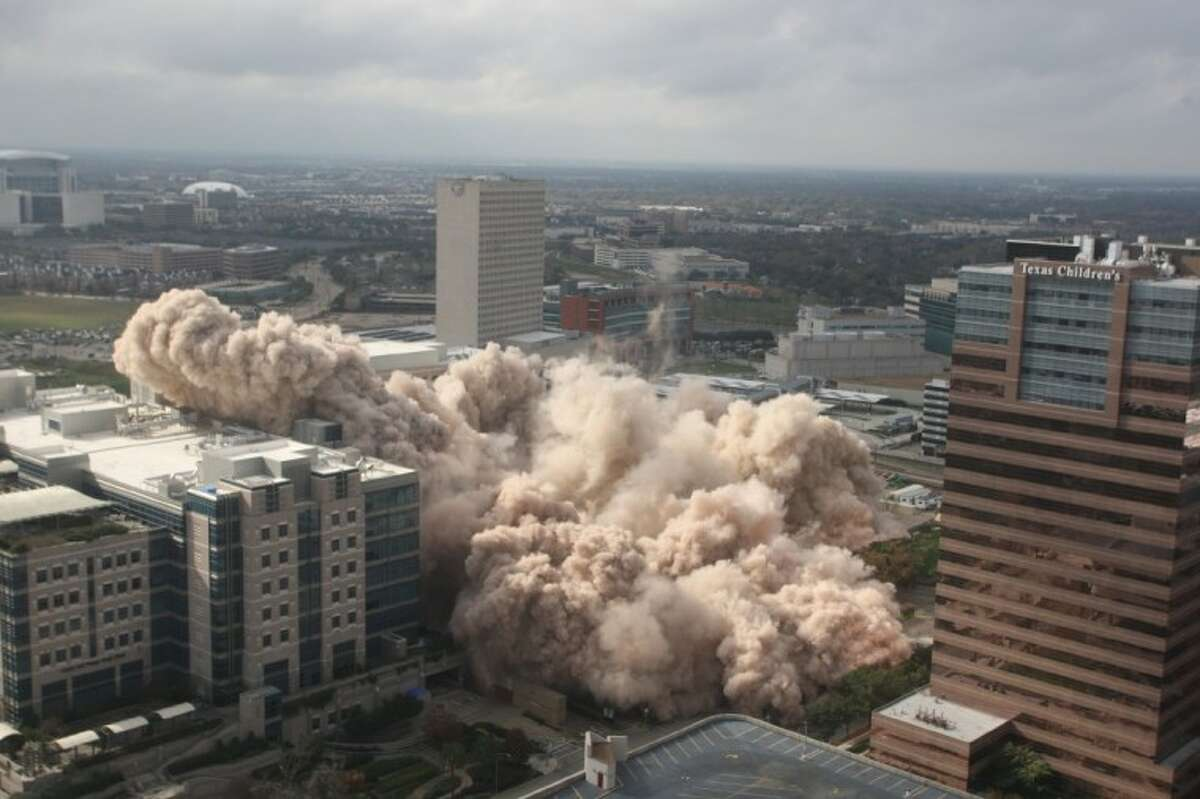 The historic Prudential Building in the Texas Medical Center sinks to the ground Sunday as it is imploded.