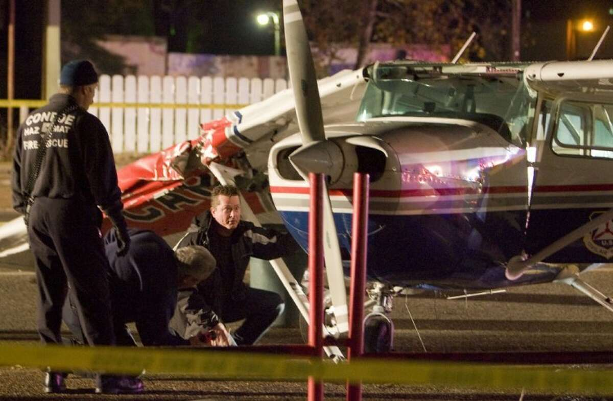 Officials examine the cockpit of a single-engine Cessna 172P after the pilot was forced to make an emergency landing Tuesday night on Davis Street.