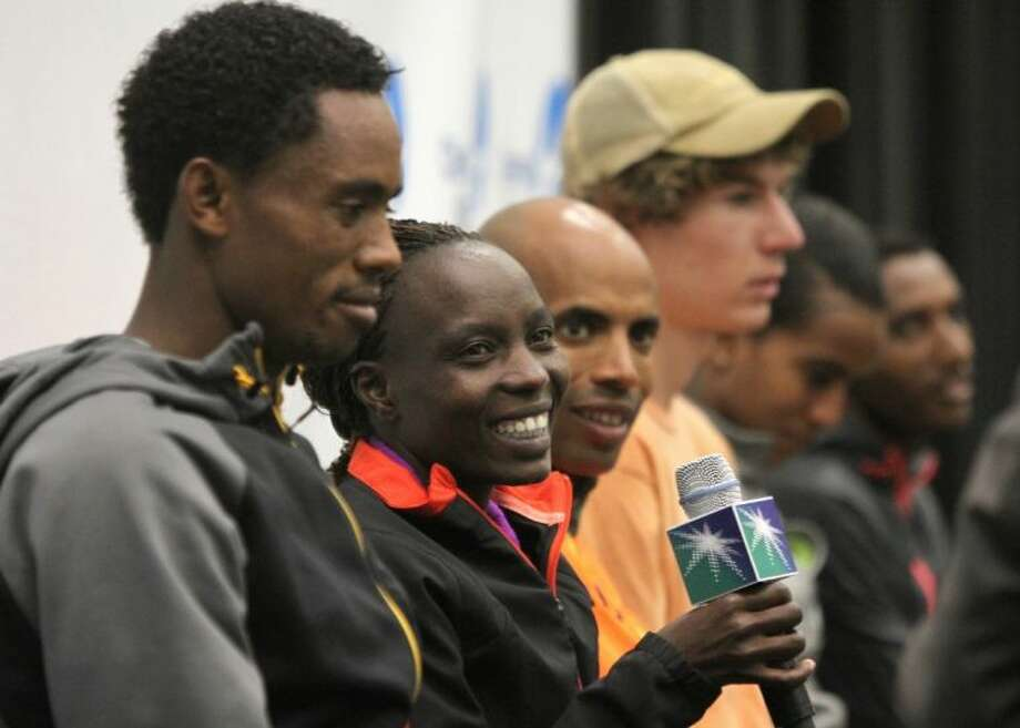 Elite runners (from left) Feyisa Lilesa, Caroline Kilel, Meb Keflezighi, Luke Puskedra, Buzunesh Deba and Bazu Worku speak Friday at the 41st Annual Chevron Houston Marathon press conference at the George R. Brown Convention Center in downtown Houston. Photo: Alan Warren / HCN