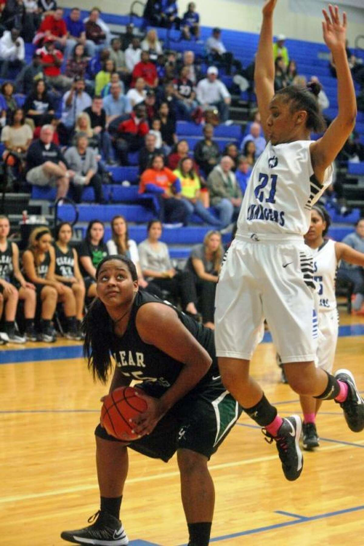 Clear Falls post Erin Farmer fakes while Clear Springs' Ryshinique Ball goes airborne in the teams' District 24-5A game Friday night. Farmer scored a game-high 17 points, but Clear Springs took a 66-41 victory.