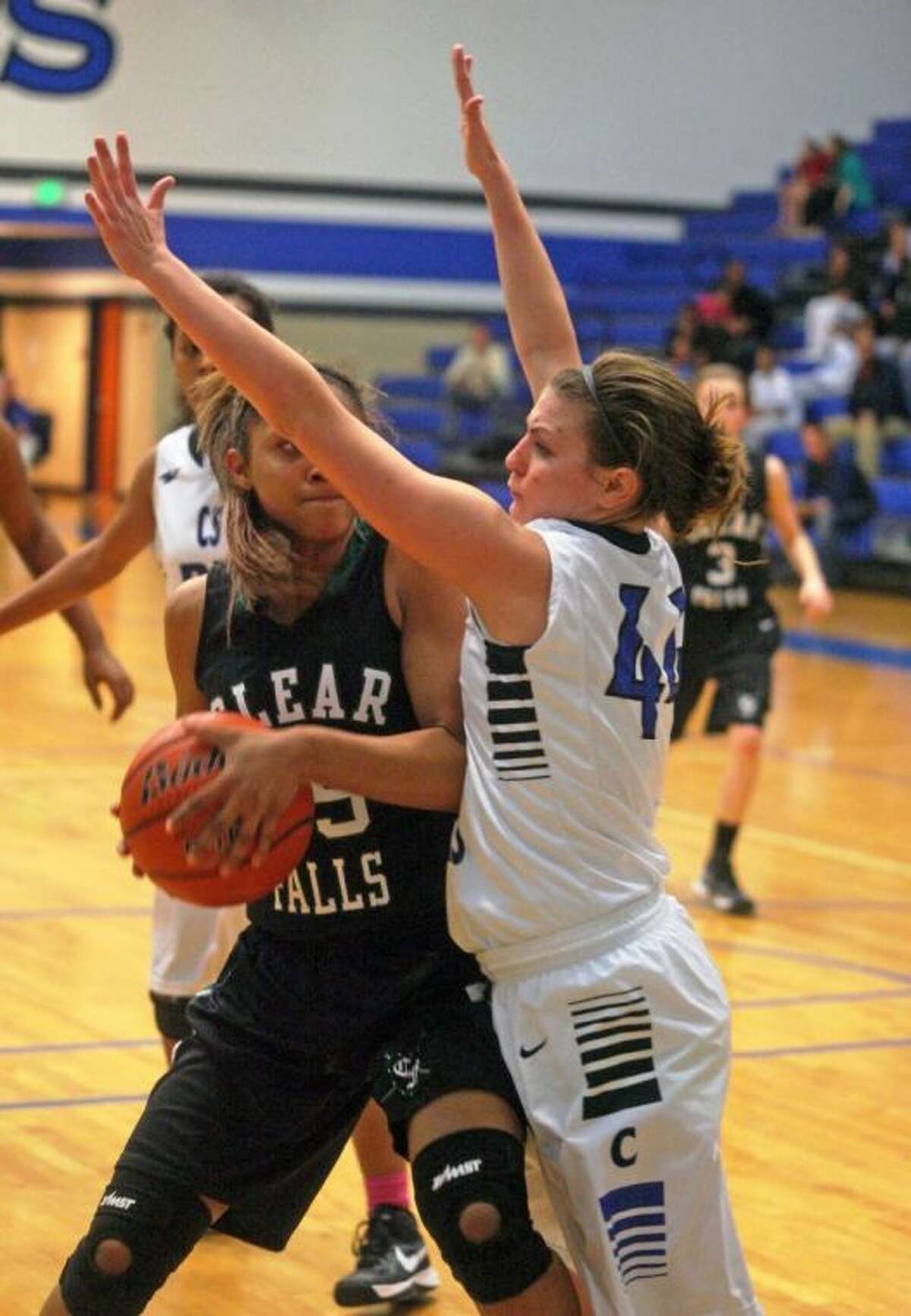Clear Falls' Ashlynn Dunbar tries to find a teammate while Clear Springs' Paige Tippet applies defensive pressure Friday night. Springs won the battle of unbeaten district teams, 66-41.