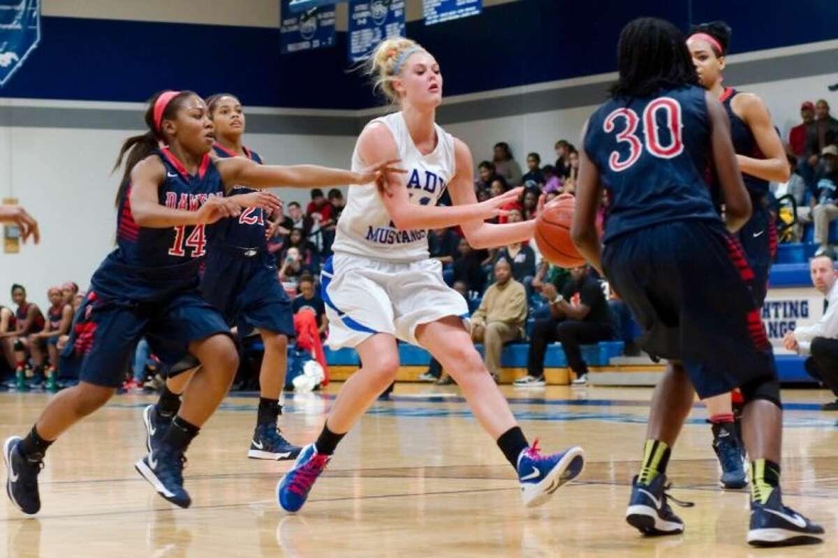 Friendswood's Jill Bergeson (11) works the ball down the court while being surround by four Dawson players. The Lady Eagles defeated the Lady Mustangs, 46-31.