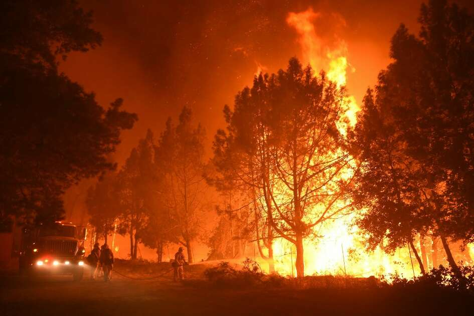 Firefighters douse flames as they approach the Casa Loma fire station in the Santa Cruz Mountains near Loma Prieta, California on September 27, 2016. The so-called Loma Fire has charred more than 2,000 acres and burned multiple structures in the area.