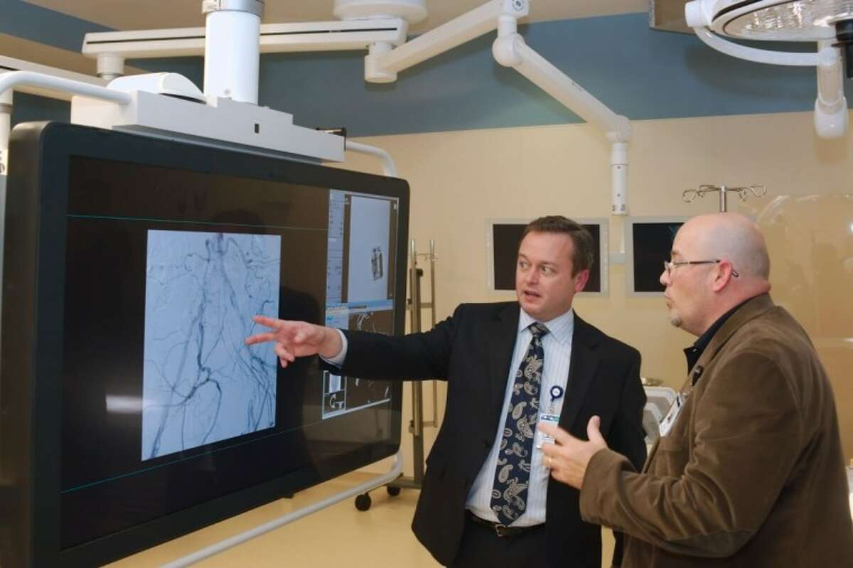 Memorial Herman Southeast hospital Endovascular Services Leader Shawn Willis, RN, and CFO Glenn Burnett, left, discuss the operation of a monitor available in one of the operating rooms available in the new perioperative services facility expansion Tuesday, Jan. 8.