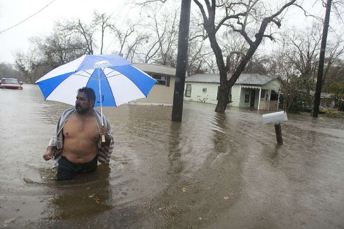 Fabian Reza wades through almost waist-deep water leaving his home that was flooded on Third Street in Richmond on Monday morning. Forecasters said as much as 4.5 inches of rainfall were recorded in some areas. (photo by Patric Schneider)
