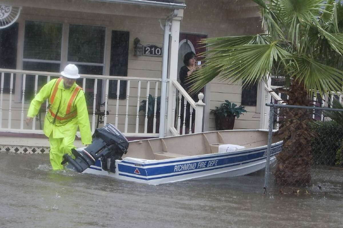 A Richmond Firefighter checks on residents that were flooded near Third St. in Richmond on Monday morning. (photo by Patric Schneider)
