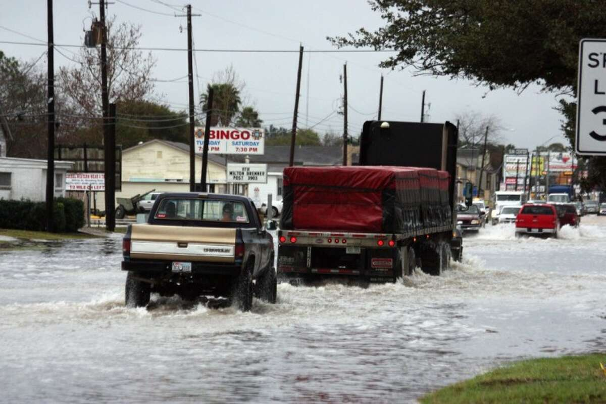 Motorists navigate a flooded portion of First Street in Rosenberg on Monday afternoon following a rainstorm that dropped more than four inches that morning.