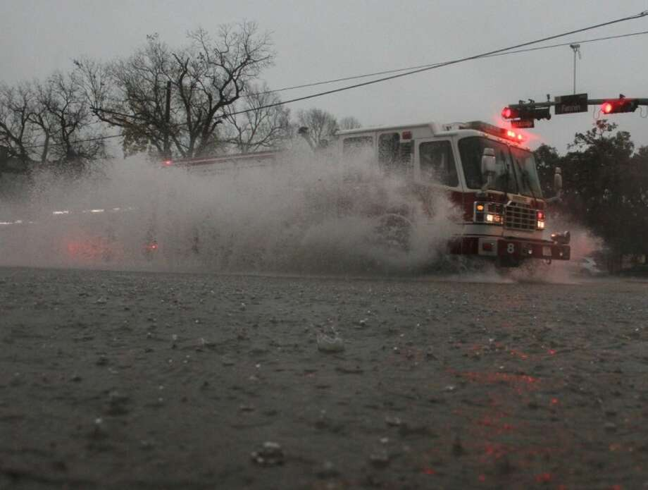 A firetruck passes through high water at the intersection of Fannin and Main Streets in the Texas Medical Center area Monday. Numerous rescues of motorists in high water were being reported, and drivers are being encouraged to stay off the streets unless their trip is an absolute emergency. Photo: JASON FOCHTMAN
