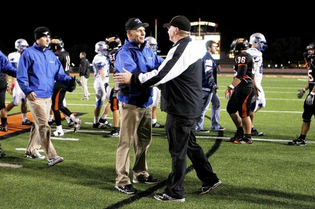 Steve Van Meter (left) and Texas City head coach Tim Finn shake hands following the Mustangs' win in the final game of the regular season that sent them to the playoffs.