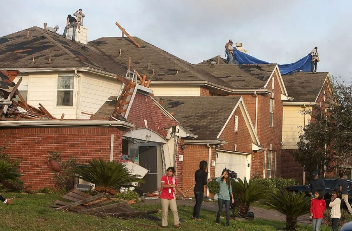 Residents clean up after a tornado tore portions of roofs off garages and homes as well as toppled wooden fences in a residential area near Bissonnet and Gaines in Sugar Land.