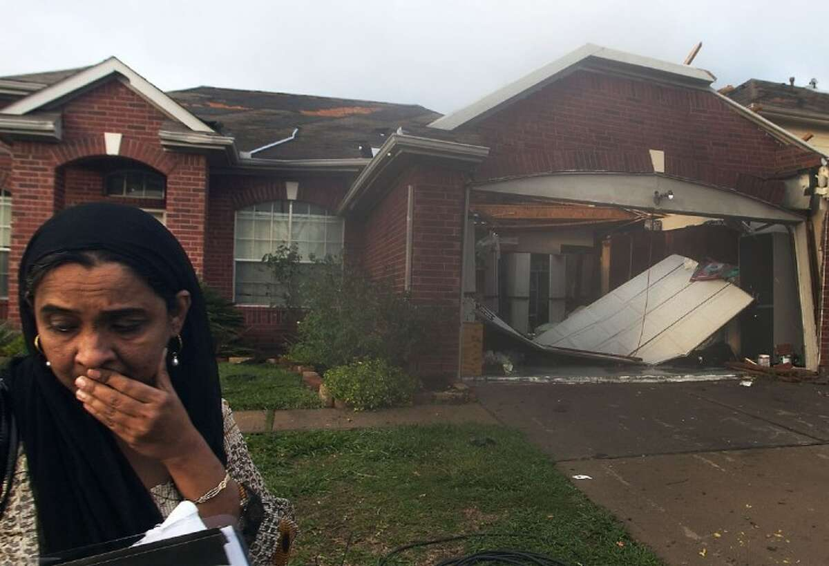 Yasmin Sayyed walks away from her home that was hit by a tornado in a residential area near Bissonnet and Gaines in Sugar Land.