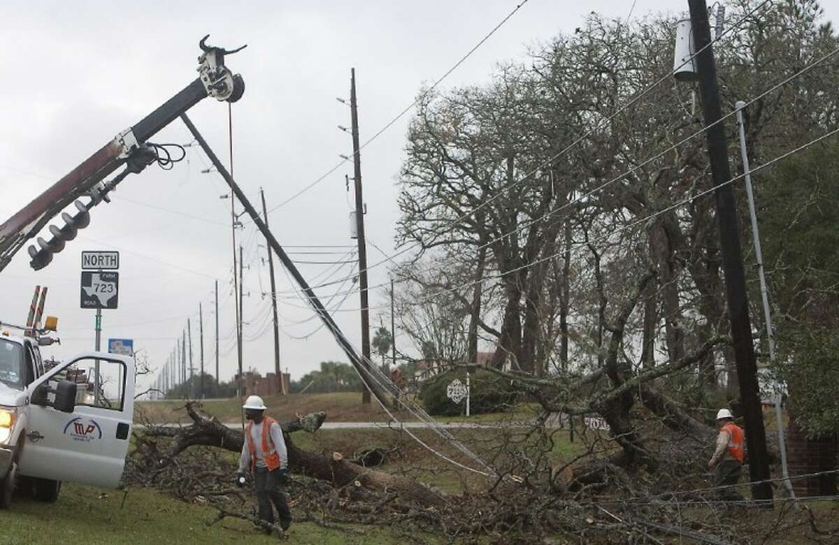 Work Crews remove a tree that fell on power lines off FM 723 near Rosenberg.