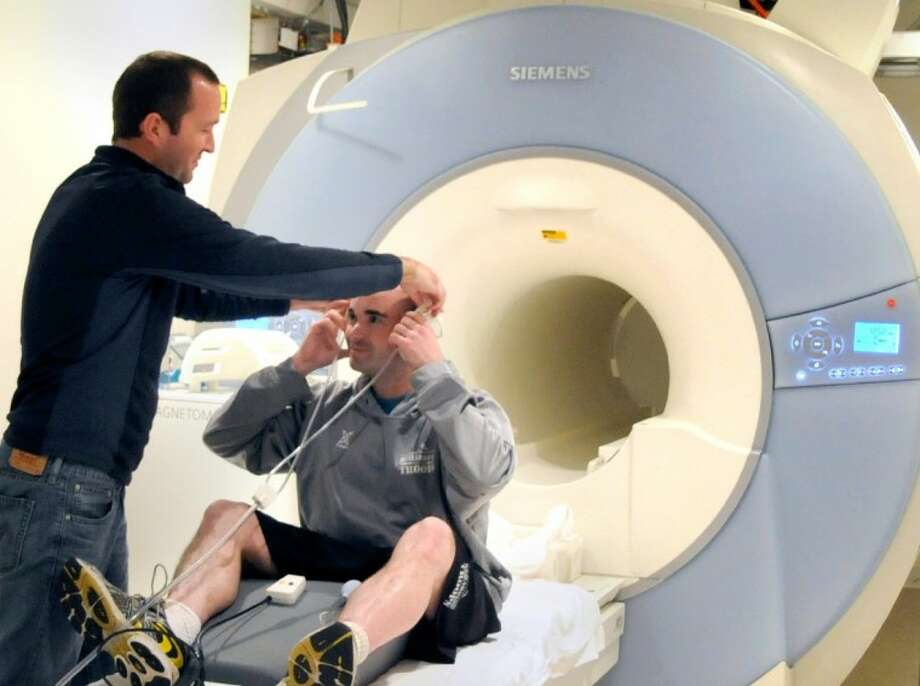 Research Coordinator Matthew Estey prepares Army Veteran Aaron Smelley for a functional Magnetic Resonance Imaging scan in order to learn how deployment affects the brain and to improve treatment of Post Traumatic Stress Disorder. (Photo by Agapito Sanchez, Jr., Baylor College of Medicine)
