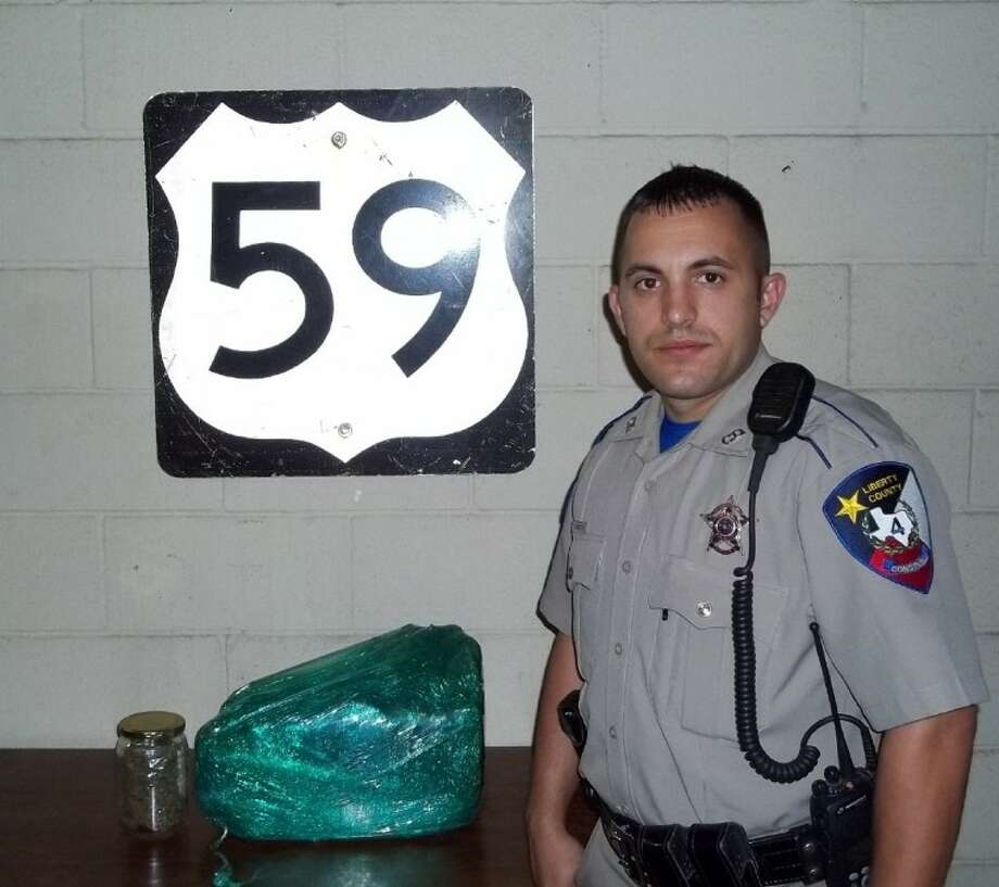 Pct. 4 Deputy Timothy Niemeyer stands next to 10 pounds seized during a traffic stop on Jan. 5 on US 59 north of Cleveland.