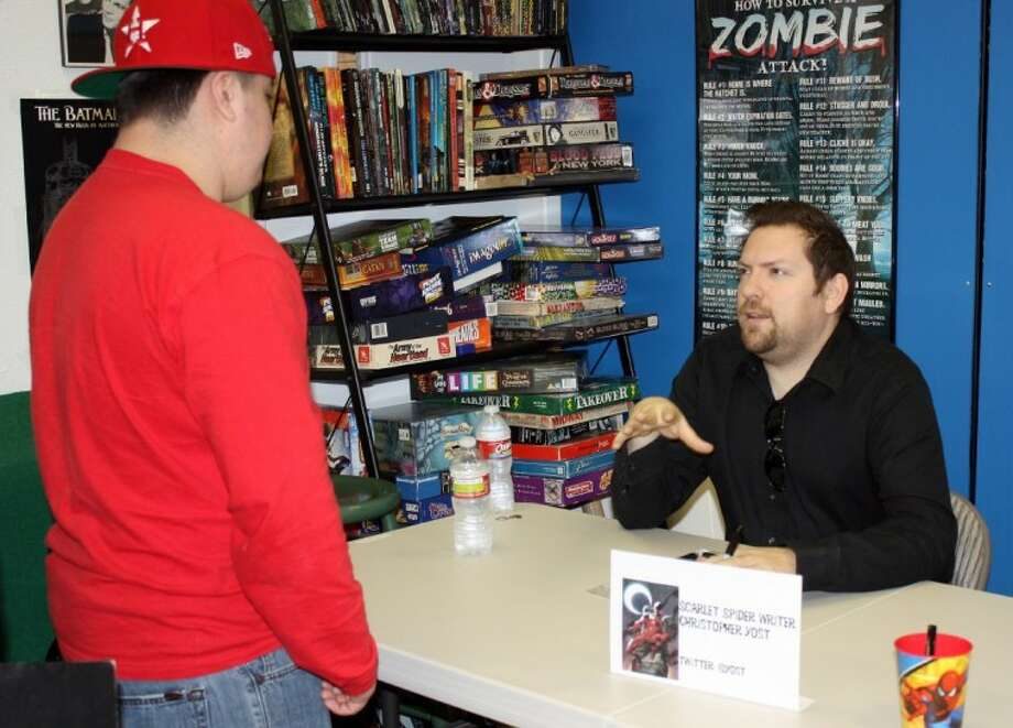 Scarlet Spider comic book writer Christopher Yost, right, visits with a fan Wednesday afternoon at an autograph session at 8th Dimension Comics & Games.