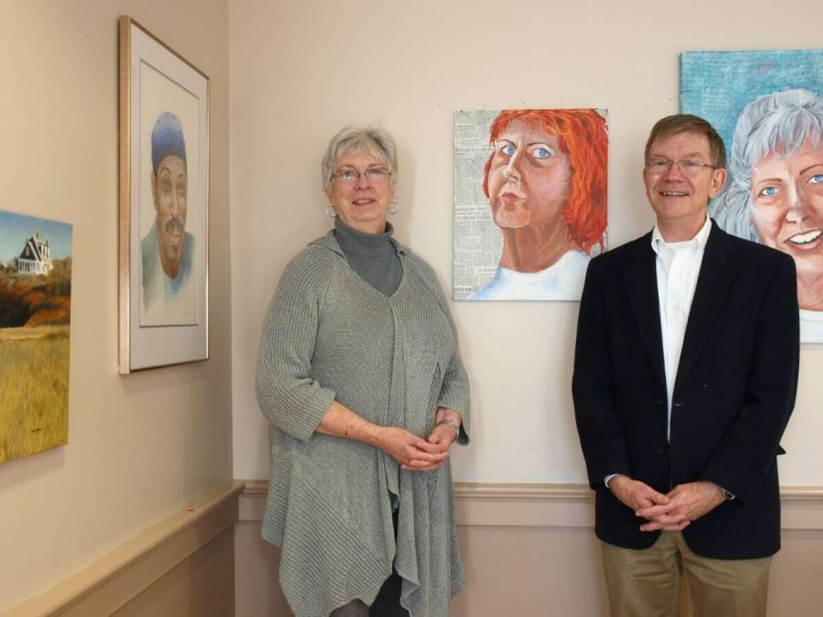 Artist Kay Cox and Kay Cox, left, and Reverend Samuel Schaal of the Bay Area Unitarian Universalist Church welcome the public to the Portraits from Life exhibit in the church's fellowship hall.