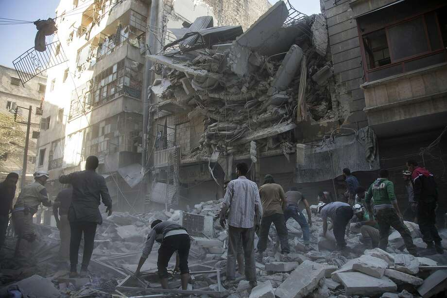 TOPSHOT - Syrian civilians and rescuers gather at site of government forces air strikes in the rebel held neighbourhood of Al-Shaar in Aleppo on September 27, 2016.  Syria's army took control of a rebel-held district in central Aleppo, after days of heavy air strikes that have killed dozens and sparked allegations of war crimes.   / AFP PHOTO / KARAM AL-MASRIKARAM AL-MASRI/AFP/Getty Images Photo: KARAM AL-MASRI, AFP/Getty Images