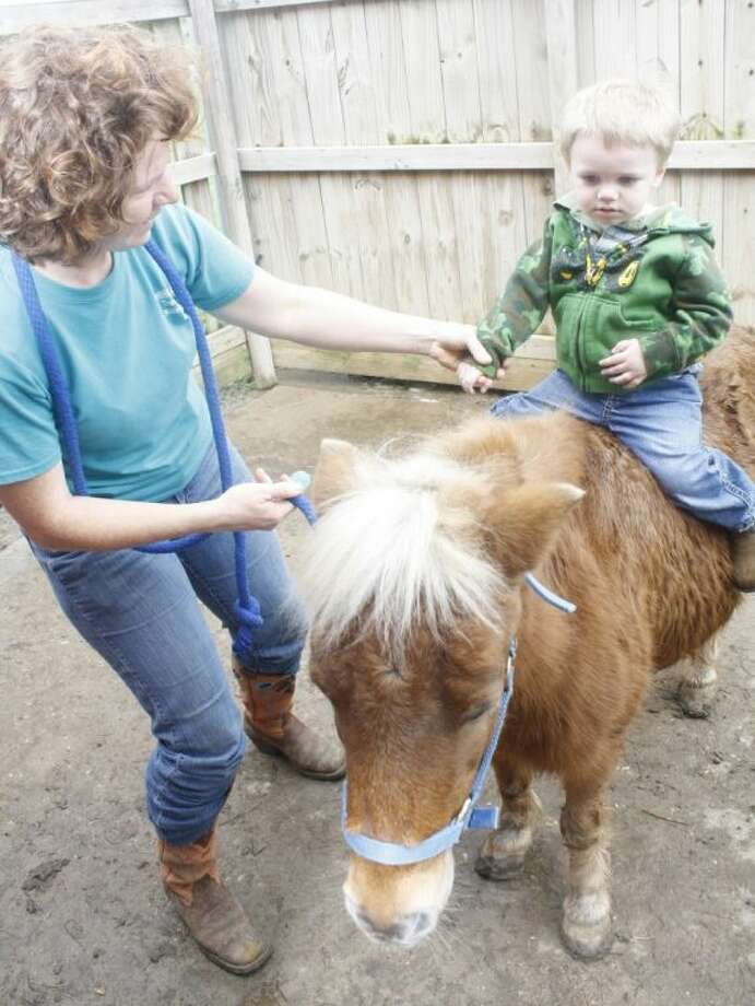 Amanda Friar, a riding instructor at SpiritHorse Therapeutic Riding Center in Liberty, helps Jake Gobert with his first horseback ride.
