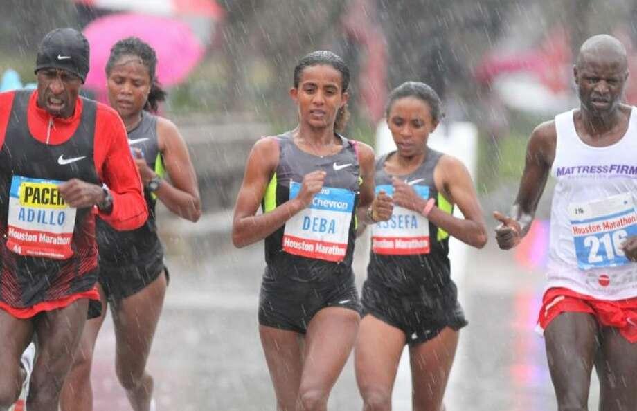 The top women leaders run through the rain Sunday along University Boulevard during the Chevron Houston Marathon. / HCN