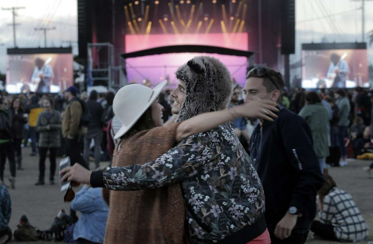 Josh Moscovitz, right, hugs friend Camille Bemer, left, during the Treasure Island Music Festival on Treasure Island, in San Francisco, Calif., on Sunday, October 18, 2015.
