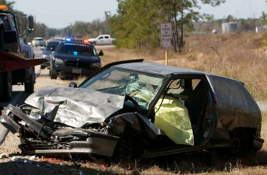 A wrecker driver looks over a vehicle involved in a fatal collision Thursday morning near the intersection of Gene Campbell Boulevard and East Industrial Parkway in New Caney.
