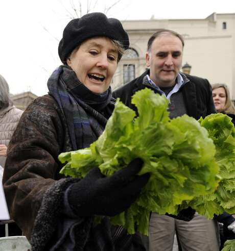 Alice Waters looks over produce at a farmers' market in Washington, D.C. Last week, first lady Michelle Obama made Waters' wish a reality when she dug a shovel into the White House South Lawn to make way for a garden. Photo: Susan Walsh, AP
